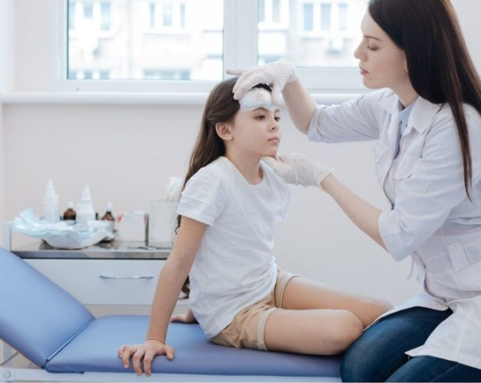 doctor examining girl's forehead
